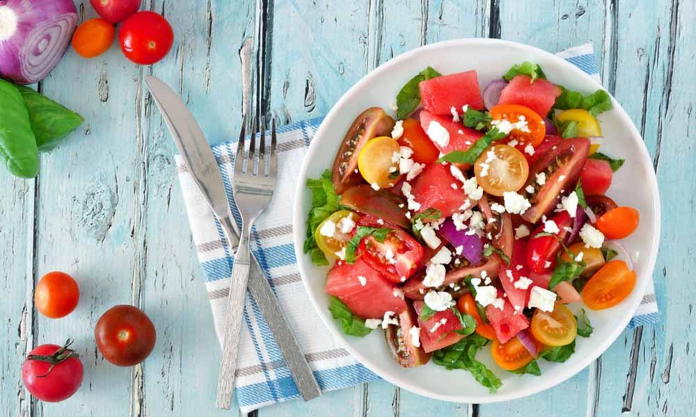 Ontbijtsalade van meloen en tomaat met feta en honingdressing